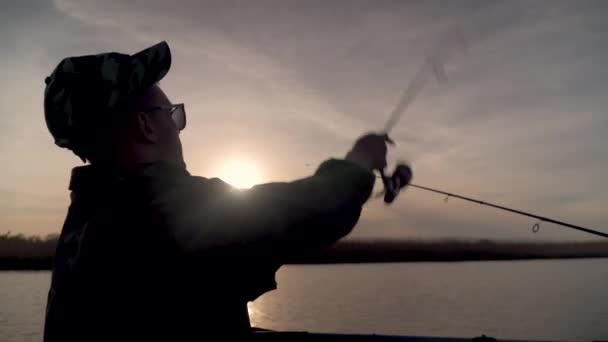 Halászat a tavon naplementekor, kilátás hátulról
