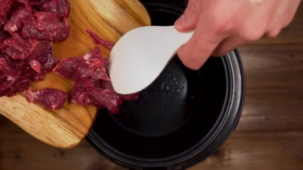 the man throws the sliced meat in the slow cooker with a spatula