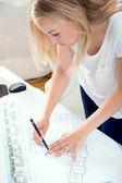 Blond architekt dělá změny v jejím projektu