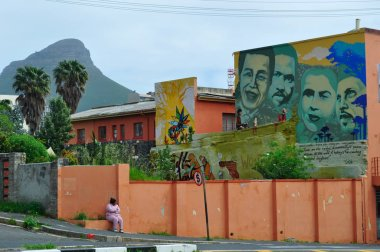 Cape Town, South Africa: a woman waiting for the bus near the mural by the famous local street artist Mak1one dedicated to the anti apartheid heroes Nelson Mandela, Steve Biko, Cissie Gool, Imam Haron