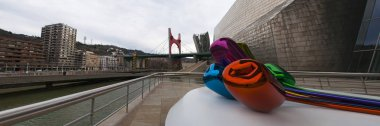 Spain: the Tulips, a bouquet of multicolor balloon flowers sculpture made by the artist Jeff Koons and located at the exterior of the Guggenheim Museum Bilbao, with view of the skyline