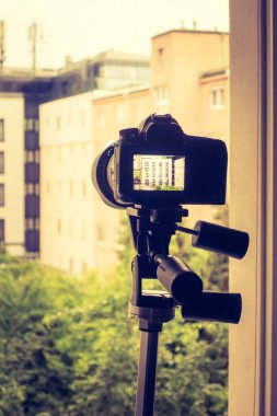 Professional with telephoto lens on tripod, surveillance and stalking
