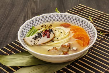 Korean noodle soup with smoked chicken and vegetables. Hot spicy dish for healthy meal. Black wooden boards background, close up