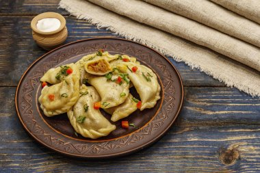 Dumplings stuffed stewed cabbage and sour cream. Traditional Ukrainian dish varenyky. Healthy vegan (vegetarian) food. Old blue wooden background