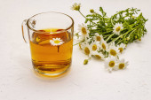 Chamomile tea. Fresh flowers, summer hot drink concept. Alternative medicine, lifestyle. White putty background, copy space