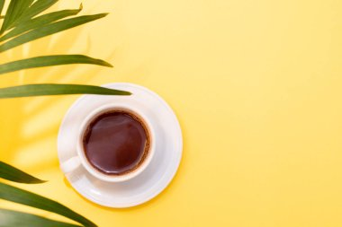 Palm leaves plant and cup of black coffee on yellow background. Copy space. Top view.