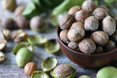 Freshly walnuts in a bowl. Harvest walnuts. Walnuts peeled from green shells. The leaves of the walnut tree.