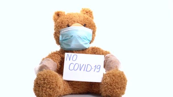játékmackó maszkban és kesztyűben, a gyógyszer szimbóluma a koronavírus ellen Covid-19