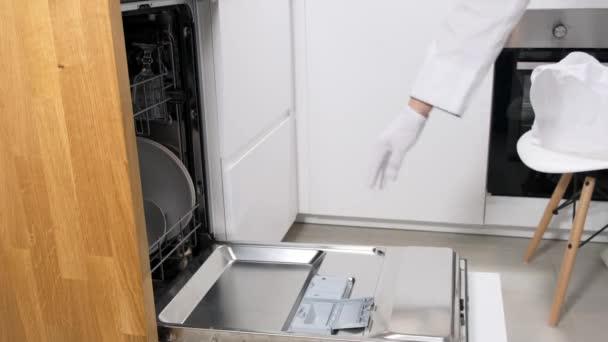 Sklenice a talíře, různé nádobí v myčce. Zavřít.