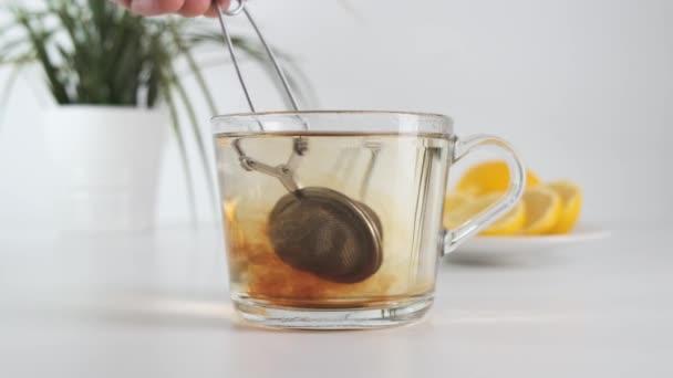 Vaření čaje ve skleněném šálku s náplní na čaj na bílém kuchyňském stole. Zavřít.