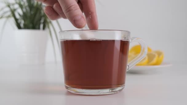 Dávám kostky cukru do skleněného čaje. Zavřít.