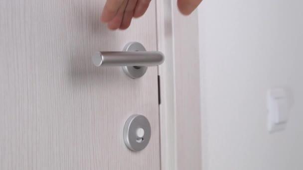 Férfi kéz kinyit fa ajtó fehér szobában. Közelről..