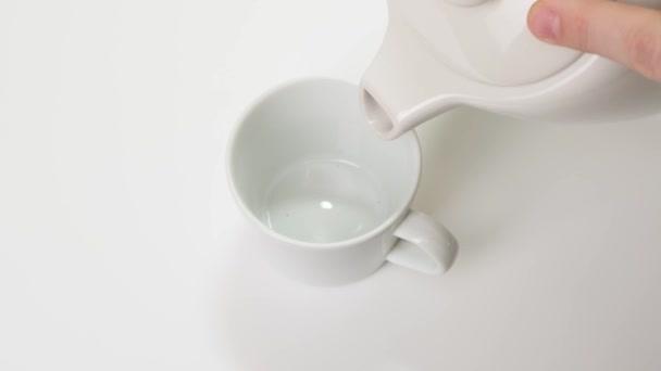 Kávébabot öntök fehér kupába. Közelről..
