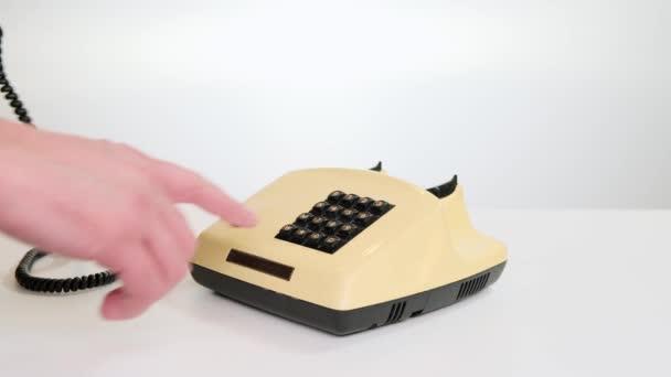 Muž prst stisk čísla tlačítka na klasickém retro telefonu na bílém pozadí. Zavřít.