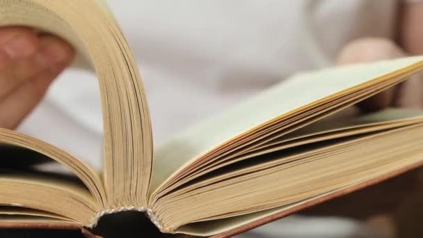 Muž listuje stránkami v knize pro prohlížení. Zavřít.