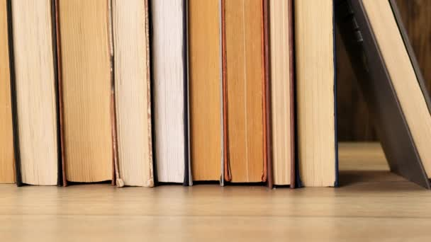 Person taking a book off a bookshelf in a library or book shop. Close up.