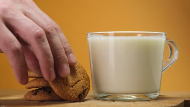 Chocolate cookies on wooden boar and glass of milk. Close up