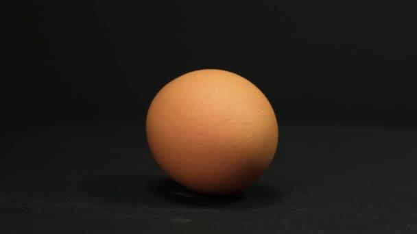 Barna tojás forog a fekete háttérben. Közelről..