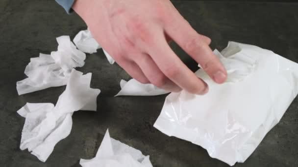 Ruka vytahuje mokrý antibakteriální ubrousek z obalu. Zavřít.