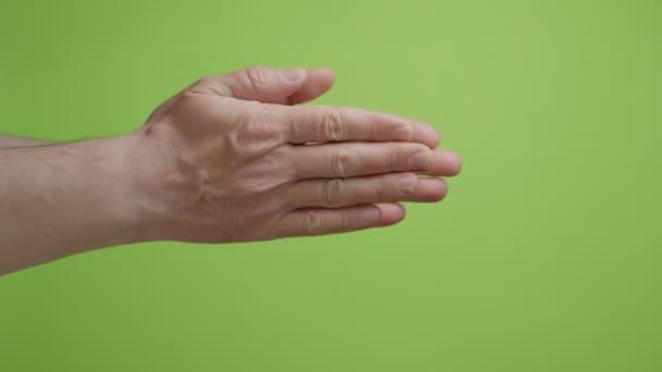 A kezek szimbólumot alkotnak. Férfi kéz taps taps zöld háttér