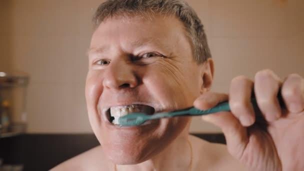 Legrační běloch kroutí obličejem a čistí si zuby