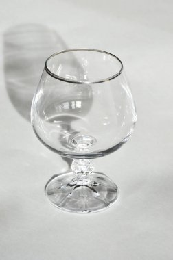 glass for alcohol, cognac on a light background. Dishes made of crystal.