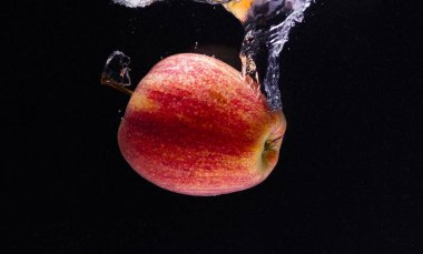 a red Apple falls into the water and creates beautiful water swirls on a black background