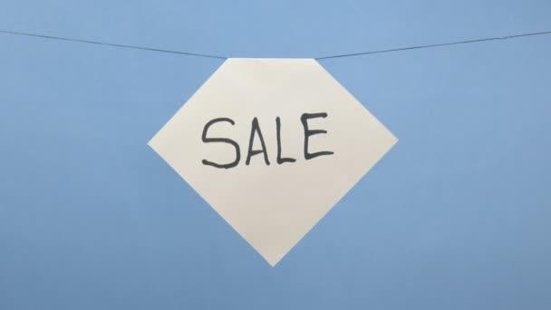 Égő és füstölgő fehér papírlap, fekete eladó felirattal, kék alapon