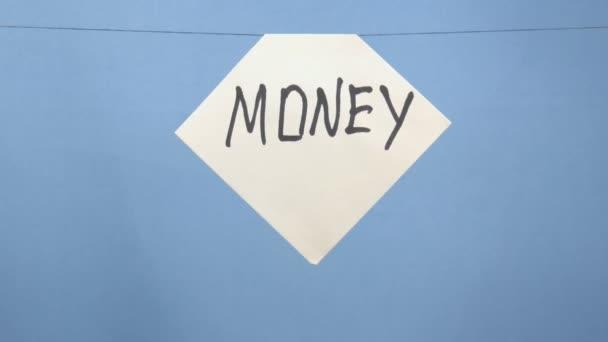 Égő és füstölgő fehér papírlap fekete felirattal pénz kék alapon