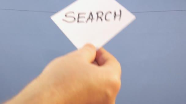 Muž pověsí bílý list papíru s černým nápisem Hledat na modrém pozadí