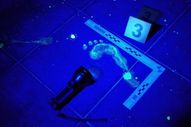 Foot print visible under UV black light on place of crime
