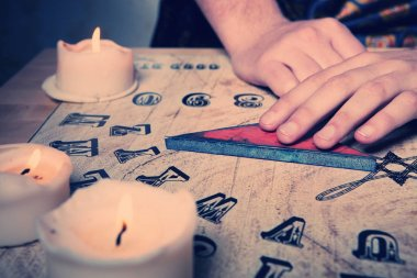 Man using ouija for communicating with human ghosts