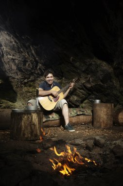 Man relaxing in wilderness with guitar near fire place