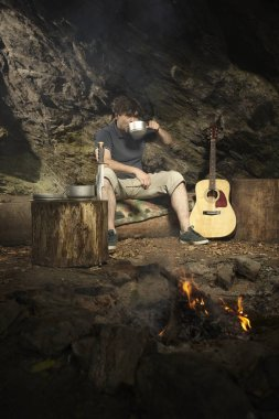 Man relaxing in wilderness with guitar near fire place and drinking
