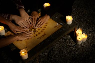 Hands of witches on spiritual board ouija