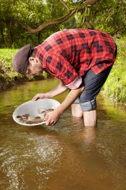 Modern prospector in hipster style panning sand in creek for gold