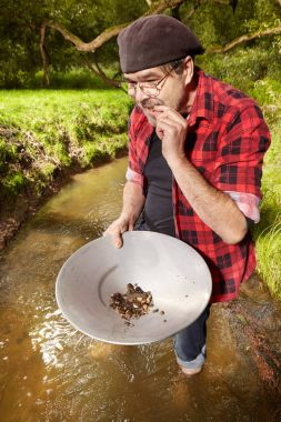 Modern prospector in hipster style panning sand in creek found gold