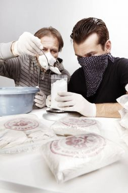 Two gang criminals weighting drugs for redistribution