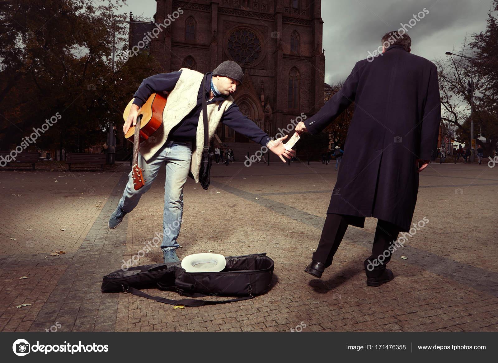 Klassische Stehlen unbekannte stehlen geld an bettler mit gitarre stockfoto