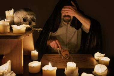 Spiritualist trying to make connection with spiritual board