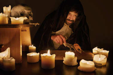 Spiritualist in middle of candles preparing summoning of ghosts