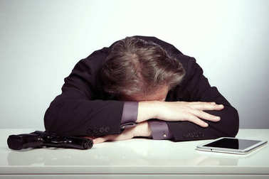Desperate manager tired about life stocks laying on table with pistol and tablet