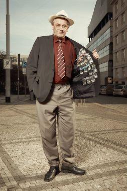 Older dealer of narcotics selling drugs hidden under suit directly on street