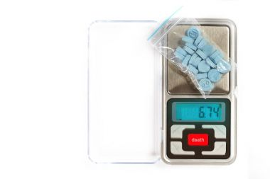 Pills of MDMA synthetic drugs on small digital scale