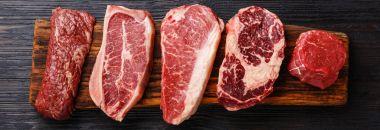 Variety of Raw Black Angus Prime meat steaks Machete, Blade on bone, Strip-loin, Rib eye, Tenderloin fillet on wooden board