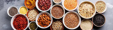Super-foods and cereals selection in bowls: quinoa, chia, goji berries, mung beans, buckwheat, bean, turmeric, polba, bulgur, lentil, sesame, flax seed, wild rice, almond on grey concrete background