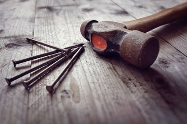 Hammer and nails on floorboards