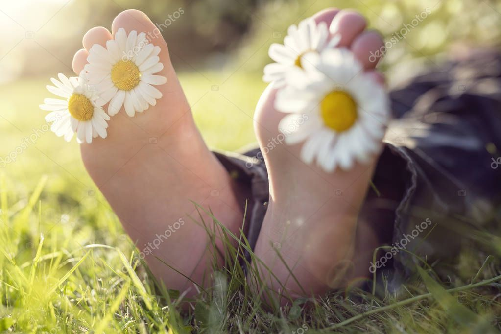 Child with daisy between toes