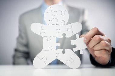 Businessman assembling jigsaw puzzle human team employee concept