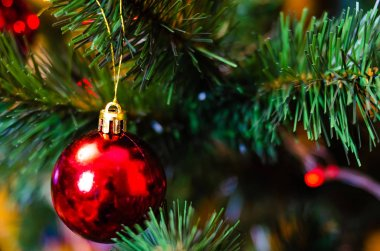 Christmas tree decoration. Balls, stars garland on a tree. Red bows on a New Year tree. The festive tree is decorated with bright toys. New Year mood. Merry Cristmas.